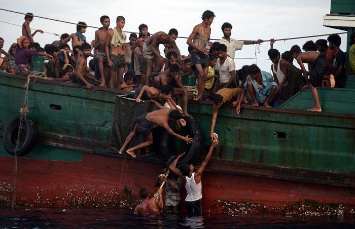 Thuyền nhân Rohingya vớt thực phẩm được thả xuống biển lên để ăn