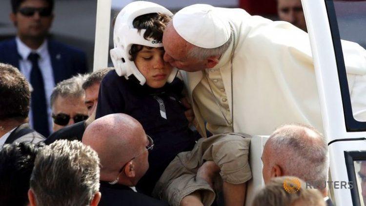 Giáo hoàng Phanxicô hôn một em bé bị bệnh trên đường đến cử hành thánh lễ tại Turin 21-6