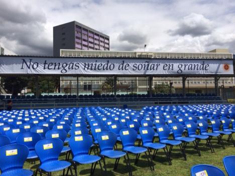 Hàng ghế được chuẩn bị sẵn tại sân bóng đá, và phía sau là băng rôn với câu nói của Đức Phanxicô: 'Đừng sợ mơ những điều vĩ đại,'