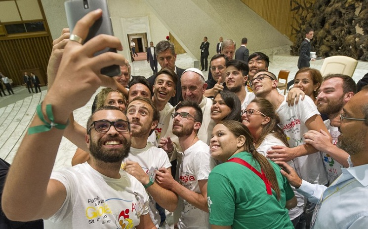 Pope Francis, center, poses for a selfie this month in Rome (PA)