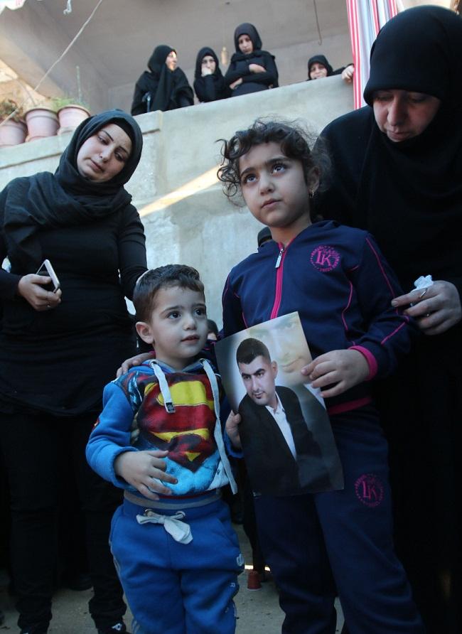 Ali và Malak, hai con của ông Adel Termos mang hình của cha trong tang lễ