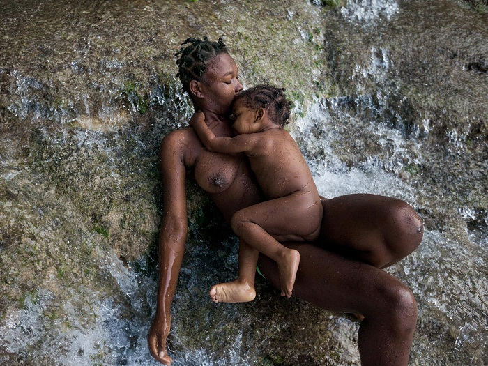 Picture of a mother and daughter bathing in Saut d'Eau falls, Haiti