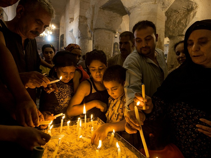 Picture of pilgrims lighting candles in Deir al Adra monastery in Egypt