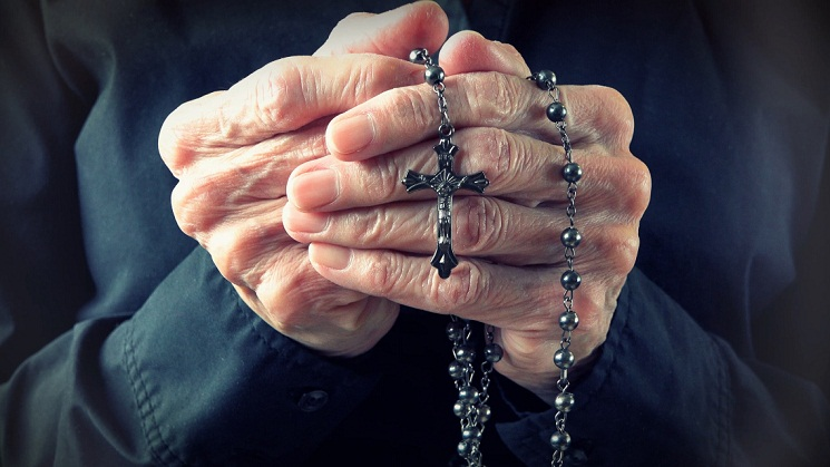 Hands of an elder woman holding a rosary while praying,