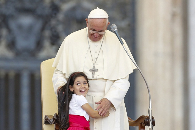 Young girl smiles as she embraces Pope Francis during audience for families participating in pastoral conference of Diocese of Rome