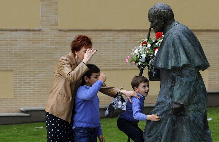 A woman and two children pray in front of a sculpture of Pope John Paul II in Oviedo