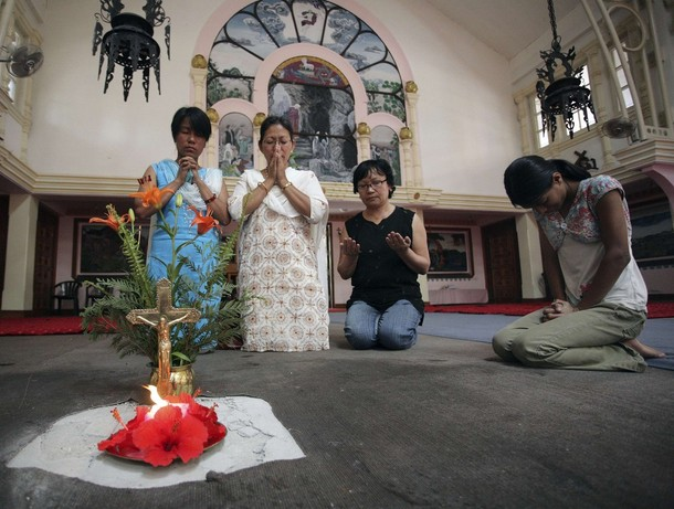 Women pray for the deceased at a blast site inside the Assumption Church in Kathmandu