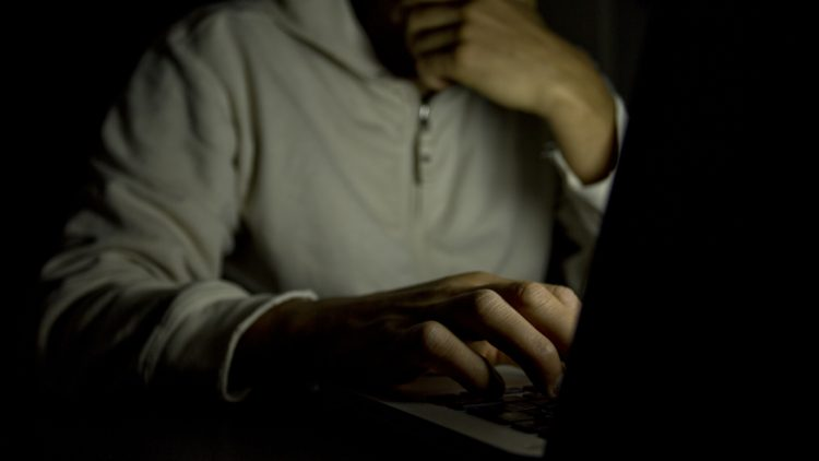 web-man-lookin-screen-dark-c2a9icsnapsshutterstock